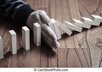 Stop The Domino Effect - A male hand stopping the domino...