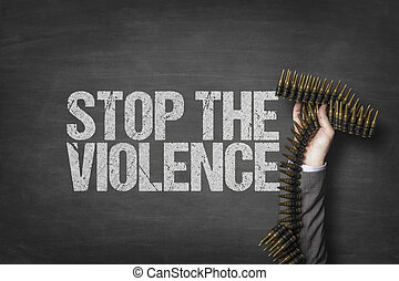 Stop the violence text on blackboard with businessman hand holding ammunition