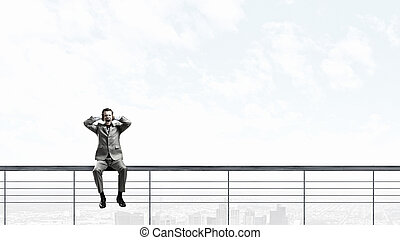 Frustrated businessman sitting on parapet closing ears with hands