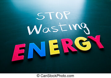 Stop wasting energy concept, colorful words on blackboard