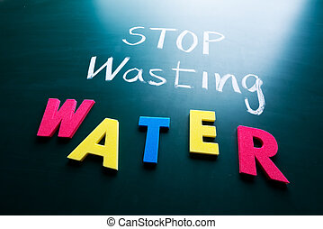 Stop wasting water concept, colorful words on blackboard