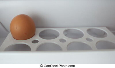 stopmotion Of Open fridge filled and put chicken eggs on a shelf of the refrigerator.