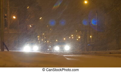 Cars waiting at the crossroads with headlights on during a snowfall in the night.