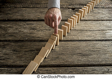 Stopping domino effect - Hand stopping domino effect of...