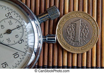 Stopwatch and coin with a denomination of 1 turkish lira on wooden table background