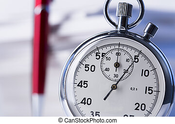 Stopwatch and pen on background of paper cards