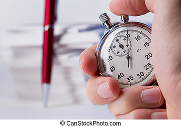 Stopwatch in hand on background of paper cards