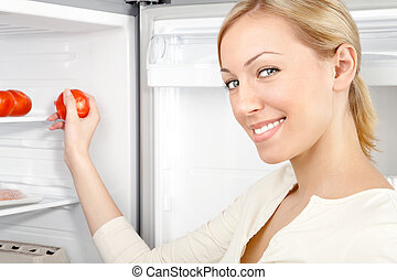 The smiling woman takes a tomato from a refrigerator