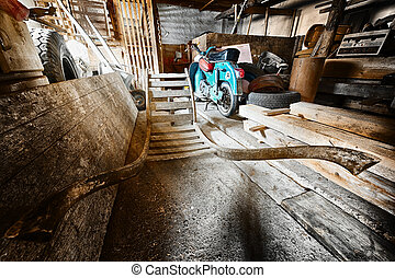 storage room in old barn with old moped and wooden barrow