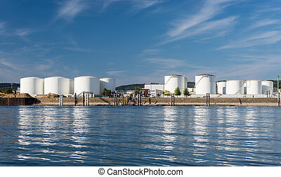 Storage silos, fuel depot of petroleum and gasoline on the banks of the river in western Germany on a beautiful blue sky with clouds.