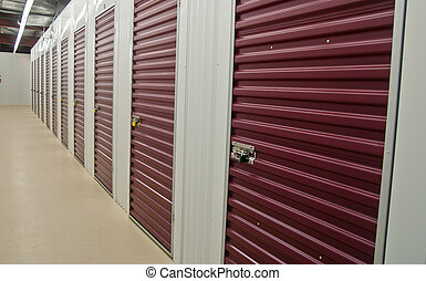 interior of storage building showing rows of individual storage units with purple doors and white walls