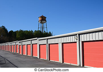 Row of storage units with water tower in the background