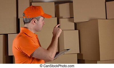 Storage worker in orange uniform counting boxes and making records in his tablet pc against brown cartons. 4K studio video