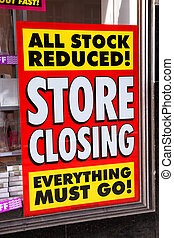 Store closing poster in a window of a bankrupt shop advertising all stock reduced