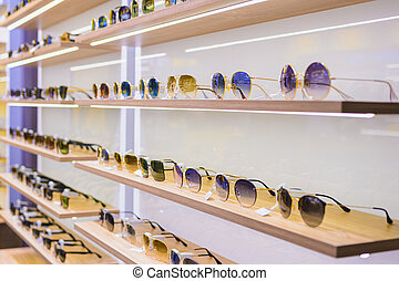 Storefront shelves of various modern sunglasses at the airport's retail store