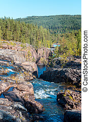 Storforsen, wild, huge waterfall on the Pite River in Swedish arctic on a sunny day of arctic summer. Norrbottens area, northwest of Alvsbyn. Wild nature of far north. Nature of Swedish Lapland.