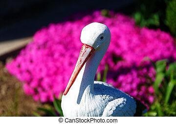 stork sculpture in garden with purple flower.