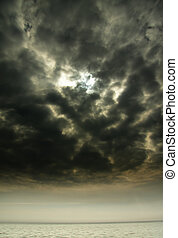 Storm approach over sea with sun hiding behind dark clouds