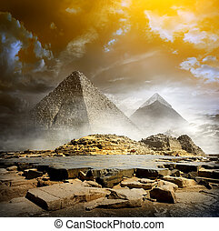Storm clouds and pyramids - Orange storm clouds and fog over...