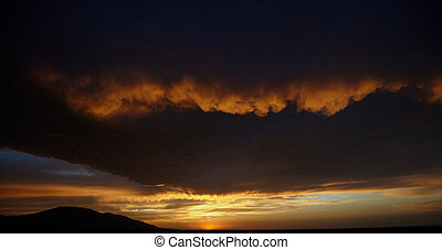 Storm clouds and sunset over mountains