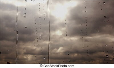 Storm clouds flying fast through the rainy window, close up view