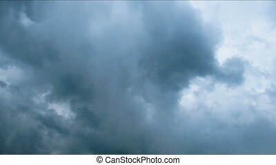 Storm clouds moving across the blue sky.