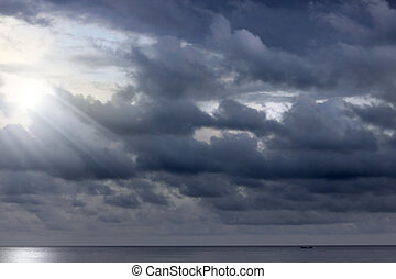 Ominous clouds above the ocean with rays of light peaking through