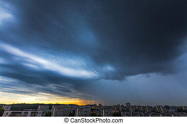 Storm clouds over the city with rain shaft
