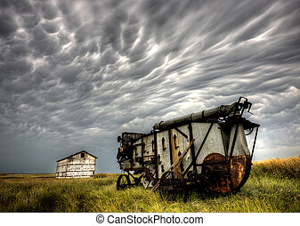 Storm Clouds Saskatchewan with abandoned old combine