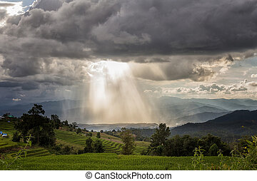 Storm clouds with rain and sunbeam over the mountain