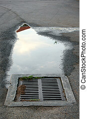 storm drain with puddle - cement and iron storm drain. There...