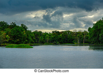 Storm dramatic clouds over a quiet forest lake