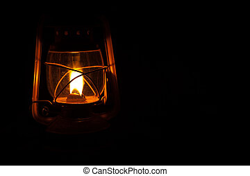 Yellow storm lantern burning at night on a wet table