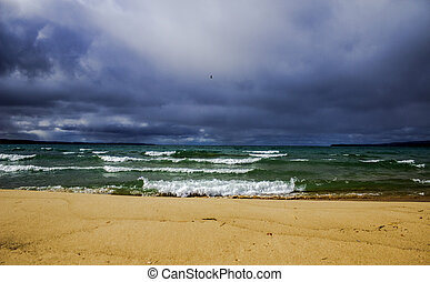 Coastal landscape with waves and a storm brewing on the horizon.