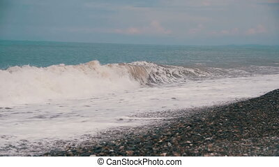 Storm on the Sea. The Waves are Rolling on a Pebble Stone Beach. Slow Motion