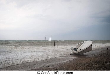 Storm on the sea with overturn boat on the beach