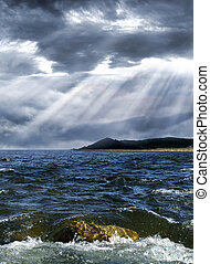 Storm over the sea - Dark clouds pierced by bright sunrays ...