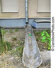 Storm pipes from a high-rise building of brown and metal color. Pipes for rainwater runoff.