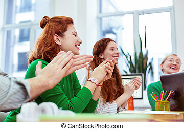 Joyful positive woman sitting with her colleagues