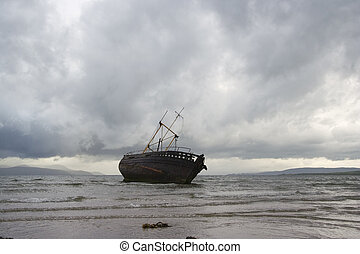 A derelict fishing boat surrounded by stormy clouds at Ettrick Bay, Bute