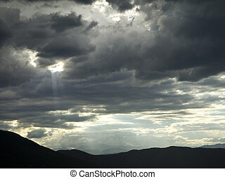 A hole in a stormy cloud let a ray of light pass through.