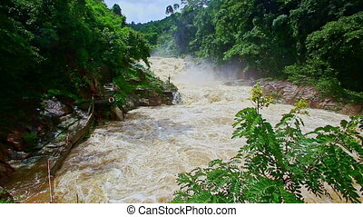 Stormy Mountain River Cascade Flows among Green Rocky Banks...
