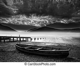 Stormy sky landscape over misty mountain lake with old boat on lake shore