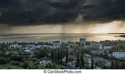 Stormy sky with dark clouds over the city and sea from above