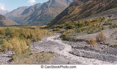Stormy stream of rocky Baksan river on mountain valley landscape from flying drone. Mountain Baksan river on Glade Azau. Reserved nature park in autumn Kabardino Balkaria aerial view