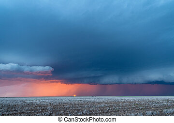 A large storm moves across the Great Plains as the sun sets behind it while rain and lightning line the horizon.