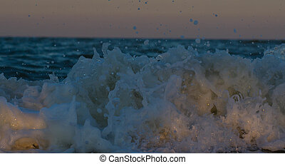 Stormy sunset at the sea. Wave and splash.