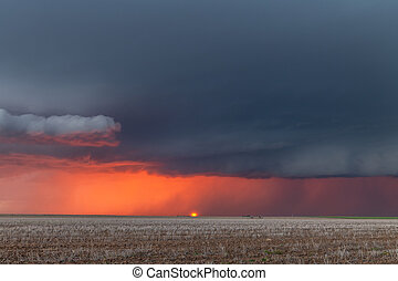 A large storm moves across the Great Plains as the sun sets behind it and rain pours along the horizon.