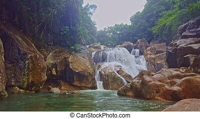 Stormy Waterfall between Rocks Falls into Pond in Tropics