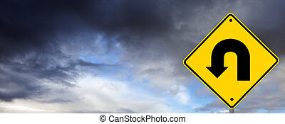 U turn road sign against storm clouds. Time to change direction.